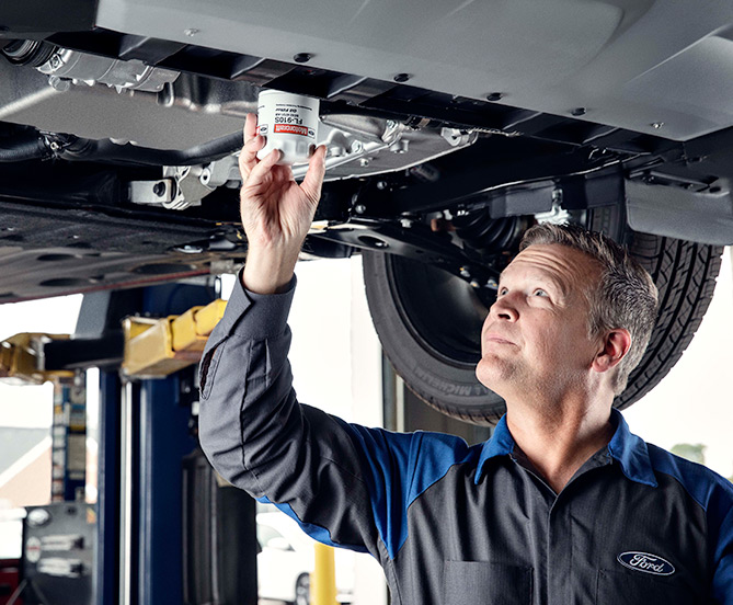 Ford mechanic working udner car