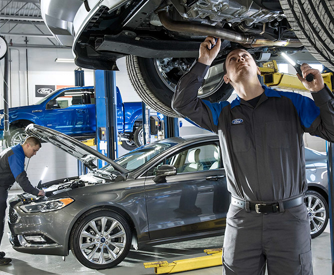 Two Ford mechanics working on different cars