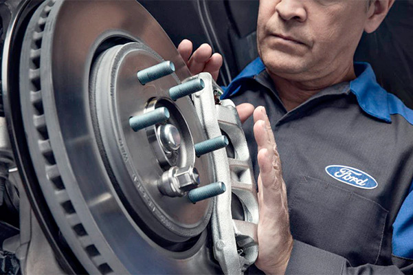 Ford mechanic inspecting brakes