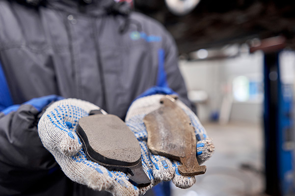 Mechanic holding new and used brake pads