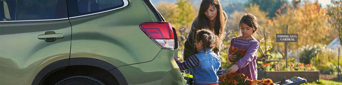 a mom and two daughters placing flowers in the back of a green subaru forester suv