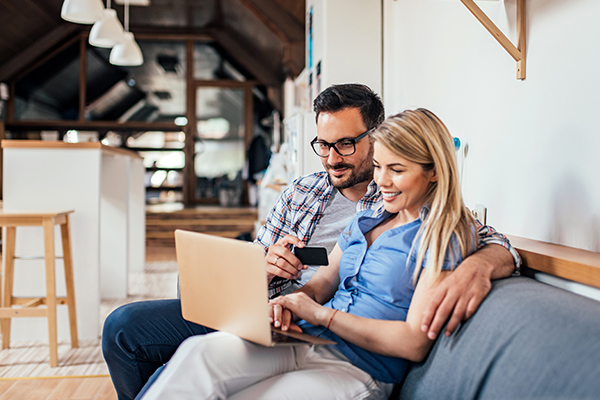 Couple shopping online while sitting on the sofa in modern apartment.