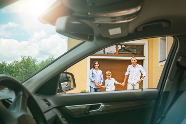 Young couple with little boy son goes to their new car standing on the new home yard inside car view