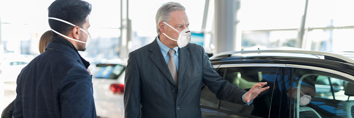 Salesman in a mask showing a car to potential customers in the showroom