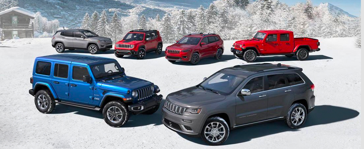 The 2020 Jeep Brand lineup: a blue four-door Wrangler Sahara and gray Grand Cherokee Summit in the front and a silver Compass Limited, red Renegade Trailhawk, red Cherokee High Altitude and red Gladiator Overland in back, all parked on a snow-covered clearing in the mountains.