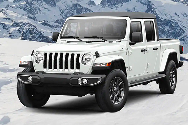 A white Jeep® Overland parked on a snow covered hill top with mountains in the background.
