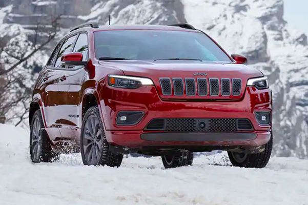 A three-quarter front view of a 2021 Jeep Cherokee High Altitude parked on snow in the mountains.