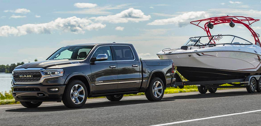 The 2021 Ram 1500 towing a boat beside a lake.