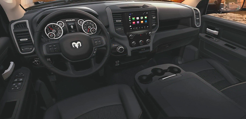 Display The interior of the 2020 Ram 2500 Tradesman featuring the steering wheel, entertainment center and dashboard.