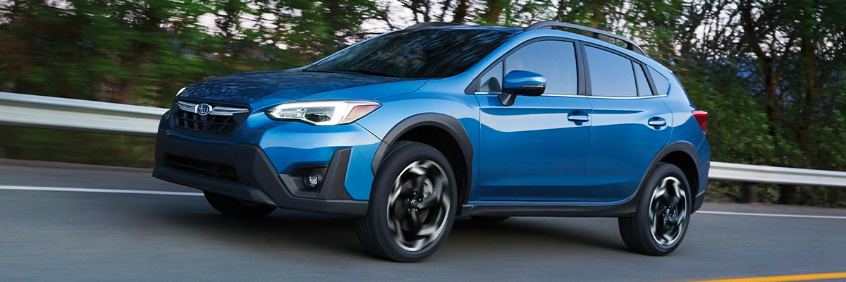 A 2020 Crosstrek shown in blue driving down road.