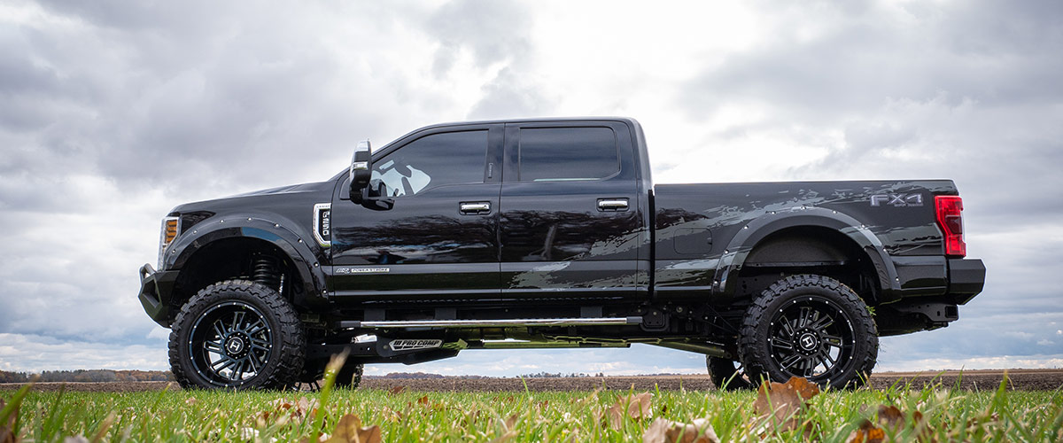side view of Ford F-350 lifted truck on a a open field
