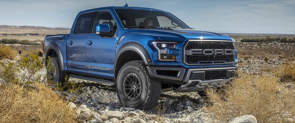 blue Ford Raptor lifted truck on a dessert background