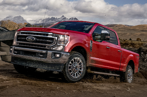 2021 Ford Super Duty F-250 LARIAT with available Chrome Package in Rapid Red at a construction site
