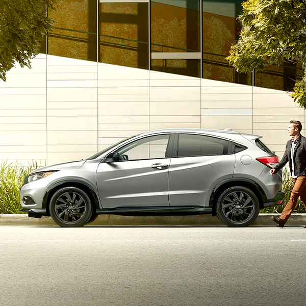 man walking beside a 2021 honda hr-v
