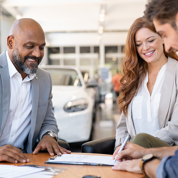 couple in dealership signing paperwork