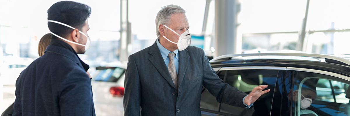 Salesperson in a mask showing two potential customers a car in the showroom