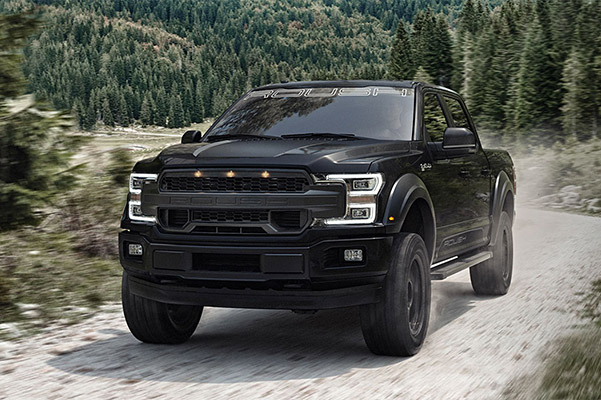 black Ford F-150 Roush Performance Vehicle going through a rough terrain road with mountains trees in the background