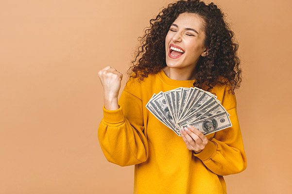 Portrait of a cheerful young woman holding money banknotes and celebrating isolated over beige background.