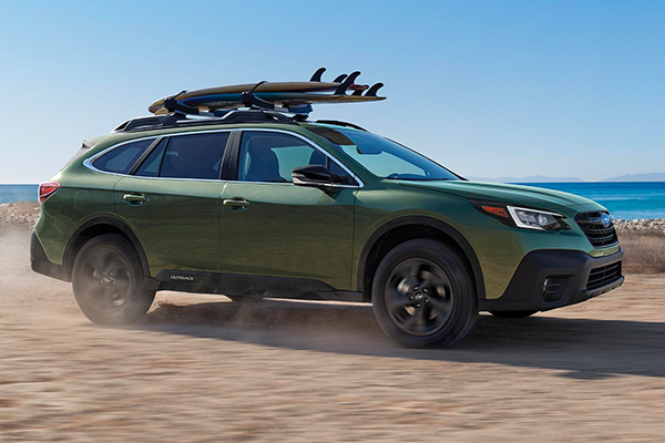 A 2020 Outback Onyx Edition XT with surf boards on its roof rack, driving along the beach.