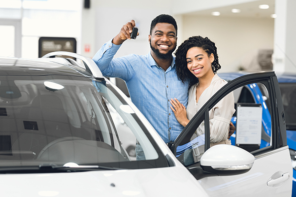 Cheerful Spouses Standing Near Car Showing Key In Dealership Center