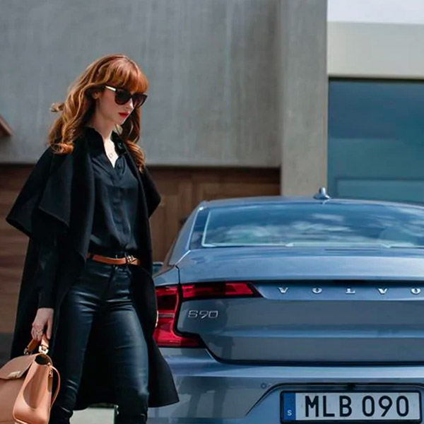 red head woman walking towards a volvo sedan