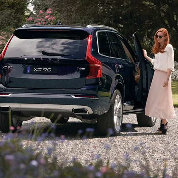 red head person next to a volvo XC90 suv in spring season