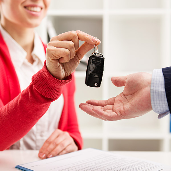 Female car agent giving key to male customer for test drive.