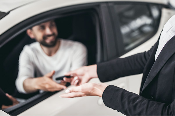Sales person handing keys to a happy customer in their new car