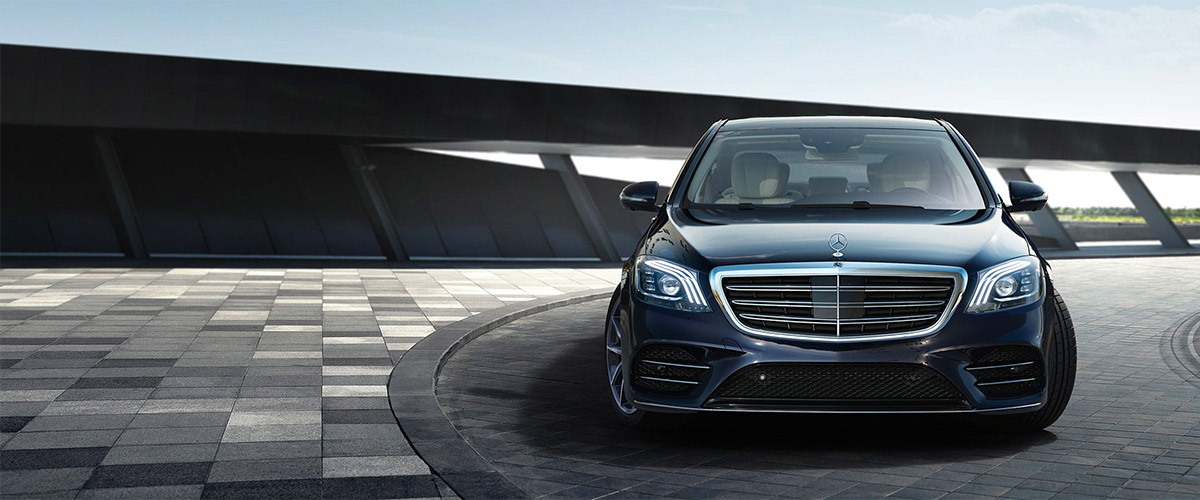 frontal exterior view of black Mercedes benz s class sedan parked on pavement and industrial achitecture background
