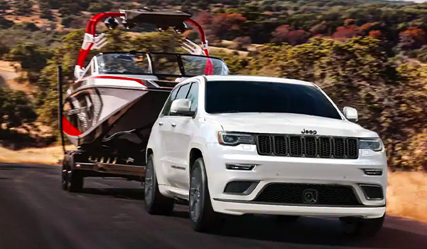 The 2021 Jeep Grand Cherokee towing a boat.