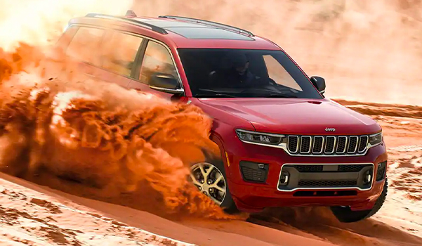 A 2021 Jeep Grand Cherokee L Overland rapidly descending a sandy hill, with dust and smoke billowing from the front and rear tires.