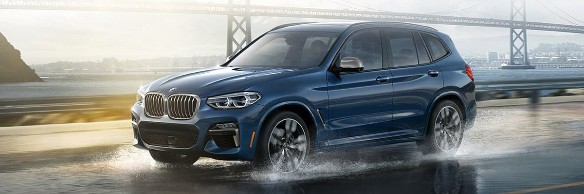 A 2021 BMW X3 in Phytonic Blue Metallic drives along a wet road in front of a bridge