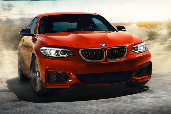 The BMW M240i in Sunset Orange Metallic enters the road with a burst of power.