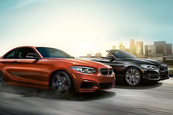 Two 2021 BMW 2 Coupes rushing ahead side by side with a cityscape background