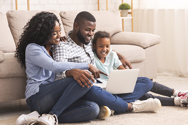 Family of three using laptop together at home